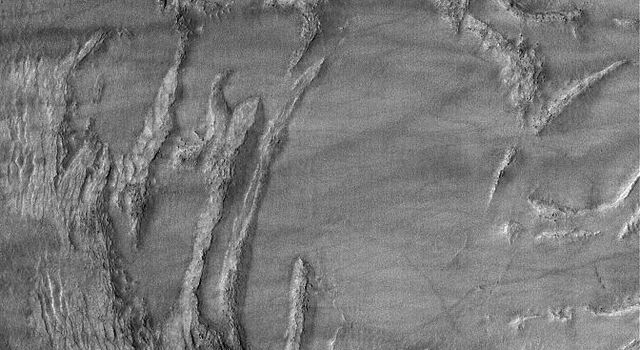 This image from NASA's Mars Global Surveyor shows complexly-eroded terrain within a partially-filled impact crater in Noachis Terra on Mars.