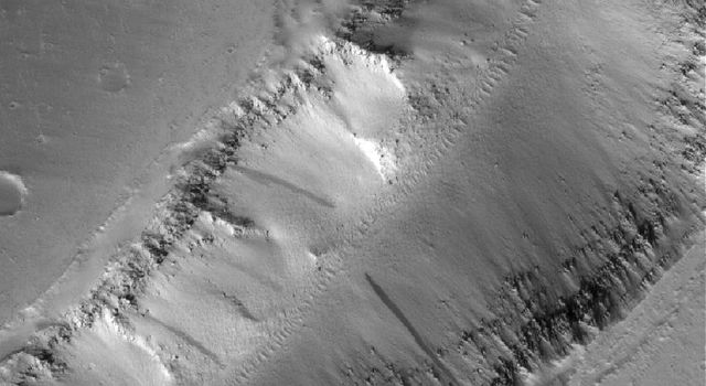 NASA's Mars Global Surveyor shows a trough formed of coalesced collapse pits in the Tractus Catena region of northern Tharsis, Mars.