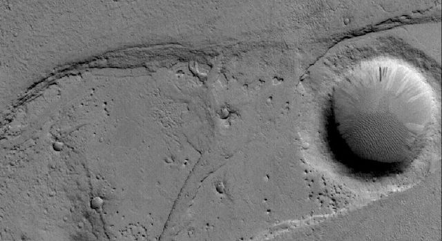 NASA's Mars Global Surveyor shows a very small portion of the hundreds-of-kilometers-long Marte Vallis system and results of catastrophic flooding. Marte is the Spanish word for Mars.