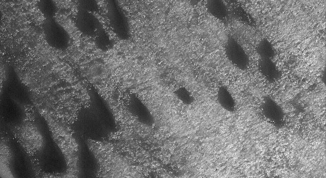 This image from NASA's Mars Global Surveyor shows a field of dark sand dunes on the northwestern floor of Brashear Crater on Mars. The dunes formed largely from winds that blew from the southeast.