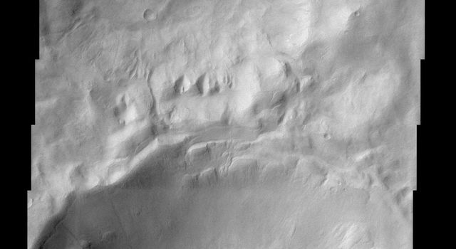 This scene shows gullies superposed on the inner walls of four large craters. Most of these gullies, imaged by NASA's Mars Odyssey spacecraft, appear to emanate from one or two specific layers along the inner crater's entire circumference.