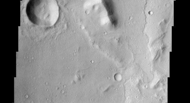 The floor of a 75 km diameter crater in the Amenthes region of Mars displays lobate flow features in the center of this image from NASA's Mars Odyssey spacecraft.
