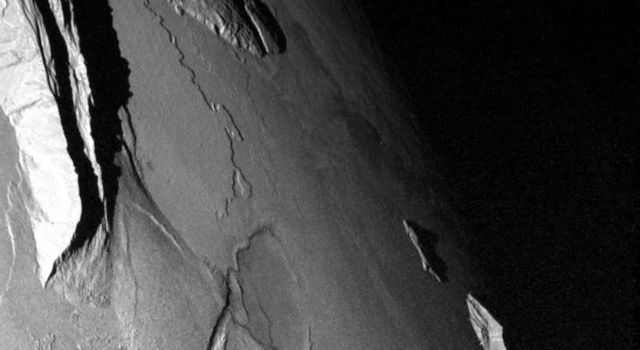 NASA's Galileo spacecraft captured this dramatic image of mountains on Io. The Sun was low in the sky. A low scarp runs from the upper left toward the center of the image. The jagged ridge is Mongibello Mons.