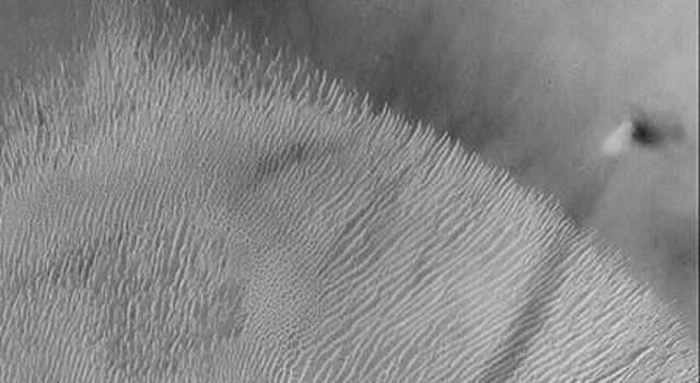 NASA's Mars Global Surveyor shows a dust devil that seen climbing the wall of a crater at 4.1°S, 9.5°W on May 21, 2002. This crater is in western Terra Meridiani on Mars.