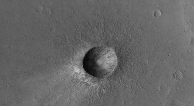 NASA's Mars Global Surveyor shows a small, relatively young impact crater in the Xanthe Terra region of Mars. Boulders can be seen in the crater ejecta deposit.