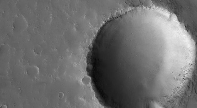 NASA's Mars Global Surveyor shows an impact crater in the volcanic Tharsis region of Mars. The margins of a lava flow are seen above the crater.