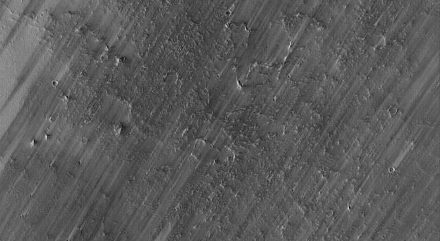 NASA's Mars Global Surveyor shows a wind-streaked plain in Tharsis near the Pavonis Mons volcano on Mars. The lighter-toned surfaces show how the plain used to look, before strong winds removed much of a thin coating of dust.