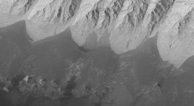 NASA's Mars Global Surveyor shows dark, windblown sand and an eroded slope of massively-bedded, light-toned, sedimentary rock. These landforms are located in east/central Candor Chasma on Mars.