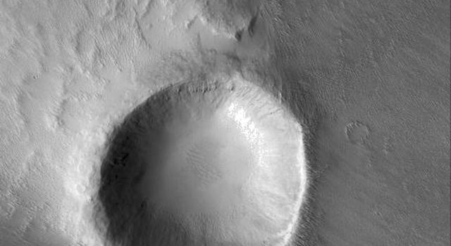 NASA's Mars Global Surveyor shows a crater in the Memnonia region of Mars, around which has formed a wind streak.