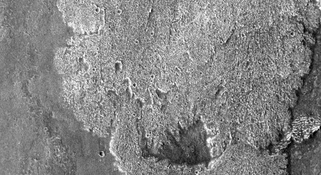 This image from NASA's Mars Odyssey spacecraft of lava flows south of Arsia Mons shows a broad, rough surfaced flow (brighter in image). The brighter flow splits at the bottom and then rejoins again, leaving a window of older flow visible.
