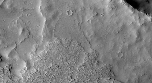 In this image from NASA's Mars Odyssey spacecraft the flows to the west of Arsia Mons (at the bottom) have started to cover the ejecta surrounding the large crater.