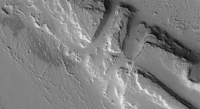 NASA's Mars Global Surveyor shows a suite of troughs in the Tharsis region that were also the site of some catastrophic floods. These features are located northwest of the volcano, Jovis Tholus.