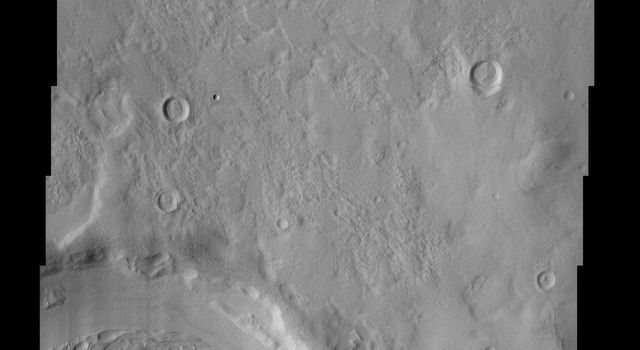 The layering of material observed at the bottom of this impact crater imaged by NASA's Mars Odyssey spacecraft suggests multiple depositional and erosional episodes in a changing environment.