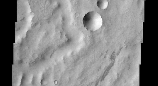 This scene from NASA's Mars Odyssey spacecraft of the dust covered plains of eastern Arabia Terra portrays a range of geological time. Three craters at the center of the image capture some of this range.
