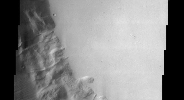 This image from NASA's Mars Odyssey shows part of the summit caldera of Pavonis Mons, the middle of three Tharsis volcanos that form a line southeast of Olympus Mons and northwest of Vallis Marineris.