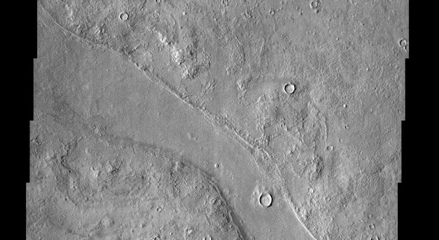A variegated mottled texture located NW of the volcano Elysium Monsis is readily apparent in the terrain imaged here by NASA's Mars Odyssey spacecraft. The Hrad Vallis channel system can be seen sauntering across the bumpy landscape of Utopia Planitia.