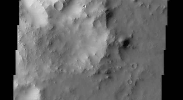 This image from NASA's Mars Odyssey spacecraft shows crater wall dust avalanches in southern Arabia Terra.