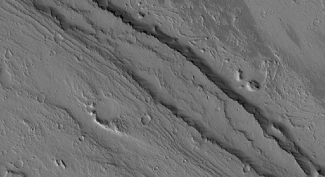 NASA's Mars Global Surveyor shows channels carved by catastrophic floods in the Tharsis region of Mars. The terrain is presently mantled with fine dust.
