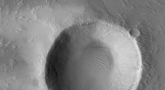NASA's Mars Global Surveyor shows an impact crater in western Daedalia Planum on Mars, with a wind streak around it.