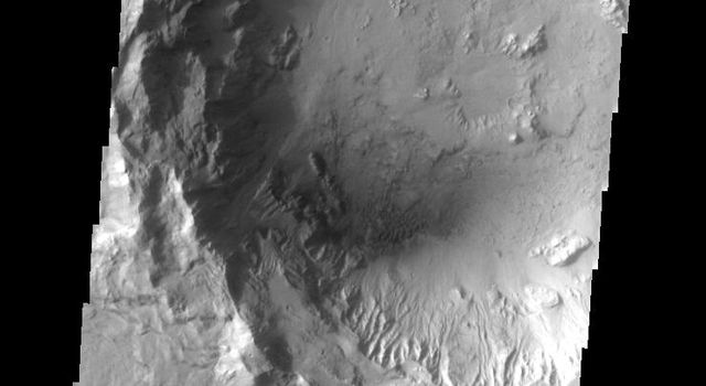 This image from NASA's Mars Odyssey shows a crater interior on Mars containing smaller craters, sand dunes, and erosional features caused the wind. Additionally, the crater rim appears subdued, likely due to dust cover.