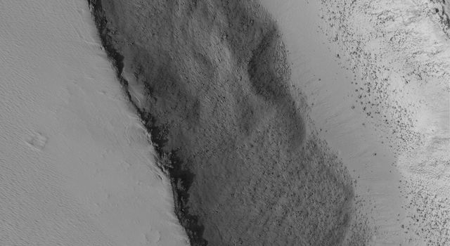 NASA's Mars Global Surveyor shows the interior of a trough, formed by faulting, on the lower southwest flank of Biblis Patera, a volcano in the Tharsis region of Mars. Boulders attest to the hardness of volcano rock, largely mantled with dust.