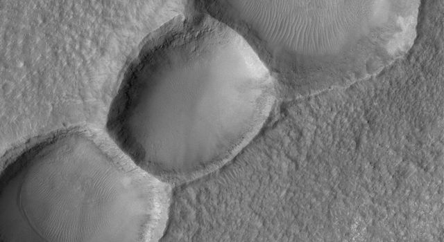 NASA's Mars Global Surveyor shows three aligned meteor impact craters on the floor of a much larger crater in the Noachis Terra region on Mars.