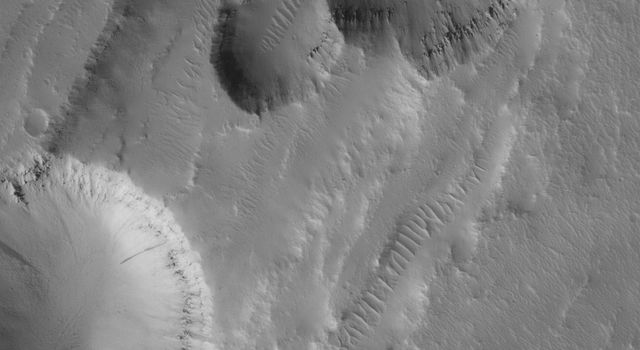 NASA's Mars Global Surveyor shows aligned pits formed by collapse along a fault trend in the Tractus Catena region of Mars, in northern Tharsis.