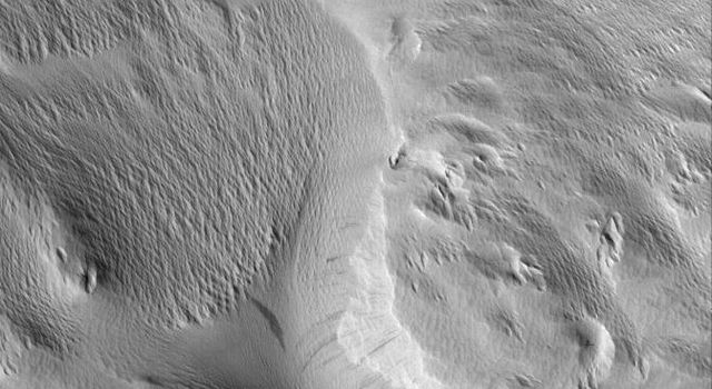 NASA's Mars Global Surveyor shows rugged terrain in the Nestus Valles portion of northern Memnonia on Mars. Wind erosion has scoured the landscape. Dust mantles the scene.