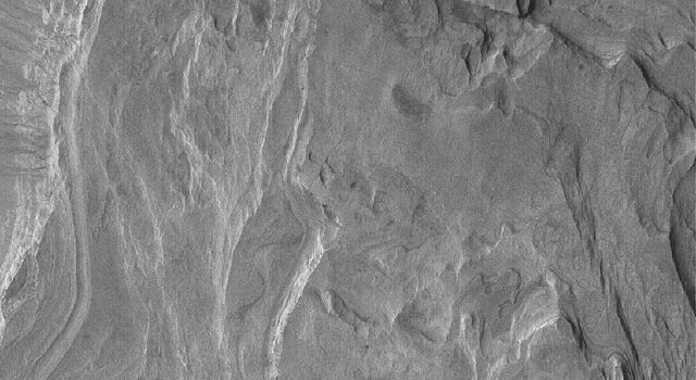 NASA's Mars Global Surveyor shows light-toned, layered, sedimentary rock outcrops in the crater, Terby. The crater is located on the north rim of Hellas Basin on Mars.