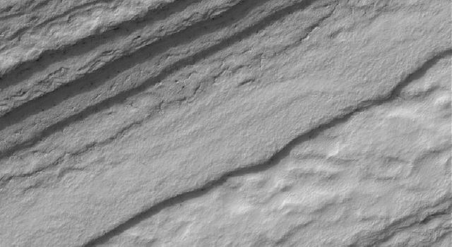 NASA's Mars Global Surveyor shows a frost-covered slope in the south polar region of Mars. The layered nature of the terrain in the south polar region is evident in a series of irregular, somewhat stair-stepped bands.