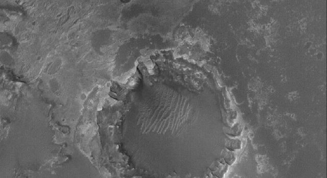 NASA's Mars Global Surveyor shows a crater formed in light-toned, layered, sedimentary rocks in Meridiani Planum on Mars. Erosion of sedimentary rock layers around the crater rim has caused an uneven retreat.