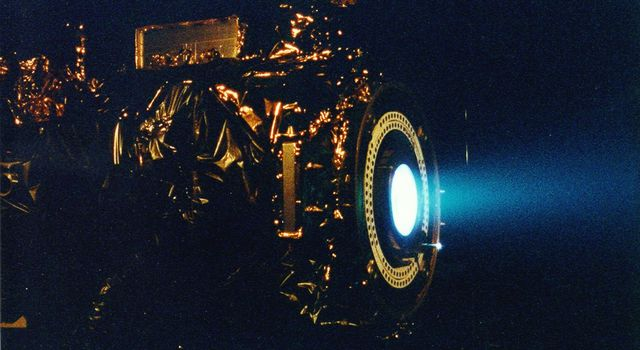 This image of a xenon ion engine, photographed through a port of the vacuum chamber where it was being tested at NASA's Jet Propulsion Laboratory, shows the faint blue glow of charged atoms being emitted from the engine.