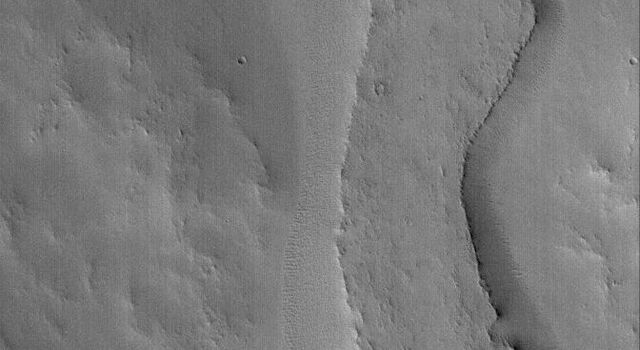NASA's Mars Global Surveyor shows an inverted valley in eastern Arabia Terra on Mars. The relatively flat-topped ridge was once the floor, or a material covering the floor, of an ancient martian valley.