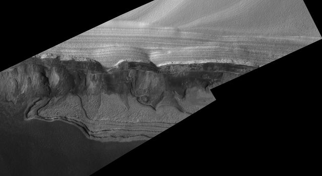 NASA's Mars Global Surveyor shows sharp detail of a scarp at the head of Chasma Boreale, a large trough cut by erosion into the martian north polar cap and the layered material beneath the ice cap.