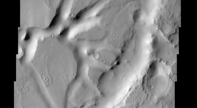 In this NASA Mars Odyssey image of eastern Arabia Terra, remnants of a once vast layered terrain are evident as isolated buttes, mesas, and deeply-filled craters.