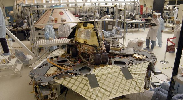 A 'Martian mechanic' checks beneath the completely deployed NASA's Rover 1 lander. Atop the lander is Rover 1 with its wheels and solar arrays in the stowed position.