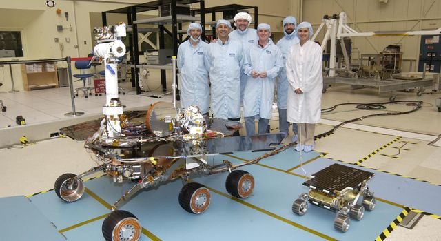 Members of the Mars Exploration Rovers Assembly, Test and Launch Operations team gather around NASA's Rover 2 and its predecessor, a flight spare of the Pathfinder mission's Sojourner rover, named 'Marie Curie.'