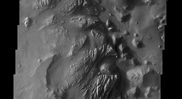 This image from NASA's Mars Odyssey spacecraft shows the easternmost end of Valles Marineris, where a rugged, jumbled terrain known as chaos displays a stratigraphy that could be described as precarious.