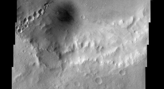 The large crater at the top of this image from NASA's Mars Odyssey spacecraft has several other craters inside of it. Most noticeable are the craters that form a 'chain' on the southern wall of the large crater.