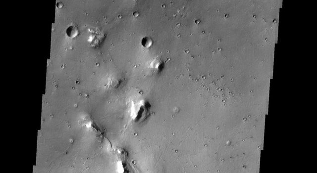 In this image from NASA's Mars Odyssey, eroded mesas and secondary craters dot the landscape in an area of Cydonia Mensae. The single oval-shaped crater displays a 'butterfly' ejecta pattern, indicating that the crater formed from a low-angle impact.