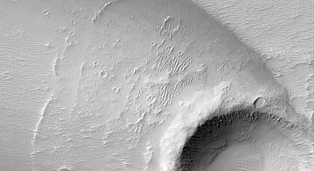 NASA's Mars Global Surveyor shows a complex streak formed by deposition and erosion of sediment by wind in the lee of an impact crater in western Daedalia Planum on Mars.