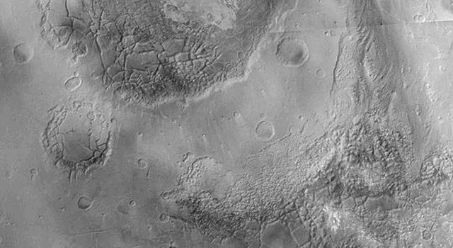 NASA's Mars Global Surveyor shows the large, circular feature Aram Chaos, an ancient impact crater on Mars filled with layered sedimentary rock that was later disrupted and eroded to form a blocky, 'chaotic' appearance.