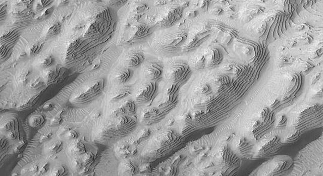 NASA's Mars Global Surveyor shows dozens of repeated layers of sedimentary rock in a western Arabia Terra crater on Mars. Dark patches are drifts of windblown sand.