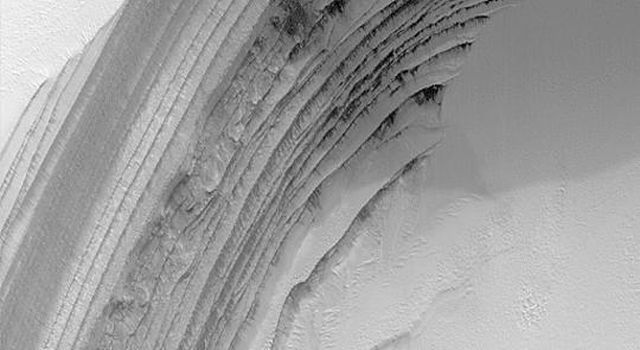 NASA's Mars Global Surveyor shows a springtime view of frost-covered layers revealed by an eroded scarp in the martian north polar cap. The layers are thought to consist of a mixture of dust, ice, and possibly sand.