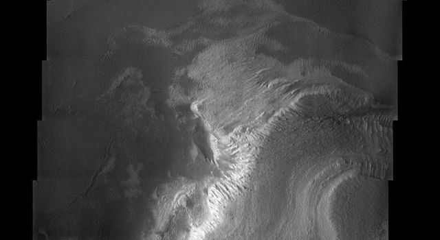 A cliff of many terraces steps down from the south to the north in this image from NASA's Mars Odyssey, showing many successive layers of material now eroded and exposed to the wind.