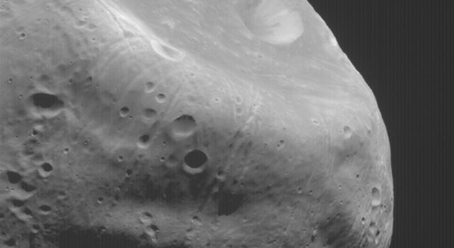 NASA's Mars Global Surveyor shows the large crater, Stickney, on Mars' moon, Phobos. Grooves, or troughs, radiate outward.