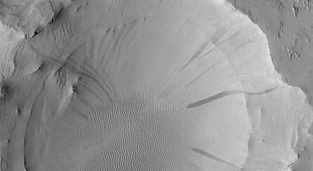 NASA's Mars Global Surveyor shows an old meteor impact crater that was once buried and was then partially-exhumed from within the layered rocks on the floor of a much larger crater in eastern Arabia Terra on Mars.