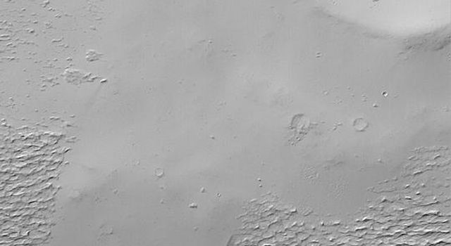 NASA's Mars Global Surveyor shows rugged, wind-eroded material that once used to completely cover the upper flanks of the martian volcano, Apollinaris Patera.