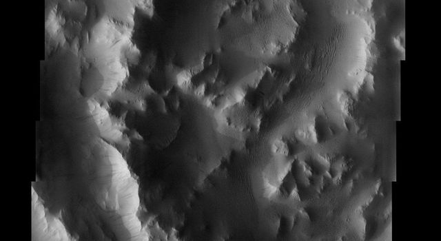 This image taken by NASA's 2001 Mars Odyssey shows rugged terrain that is part of a massive lobe of material extending from the basal scarp of Mars' Olympus Mons is called sulci, which means furrows or grooves.