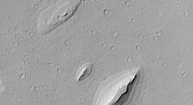 NASA's Mars Global Surveyor shows wind-sculpted remnants of layered sedimentary rock that once completely covered the northwestern floor of Henry Crater, an ancient impact basin on Mars.